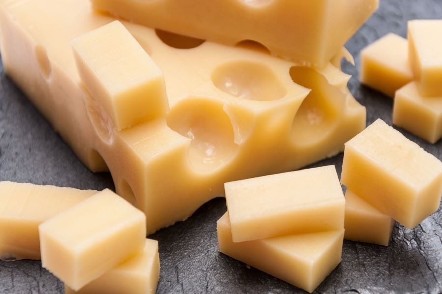 Cubes of cheese and a large piece of cheese