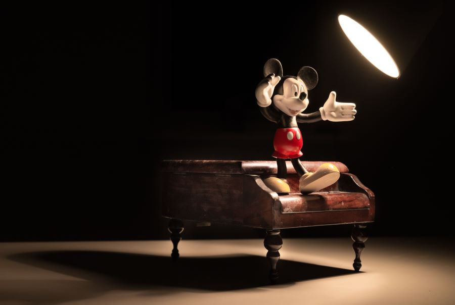 Mickey Mouse standing on a piano