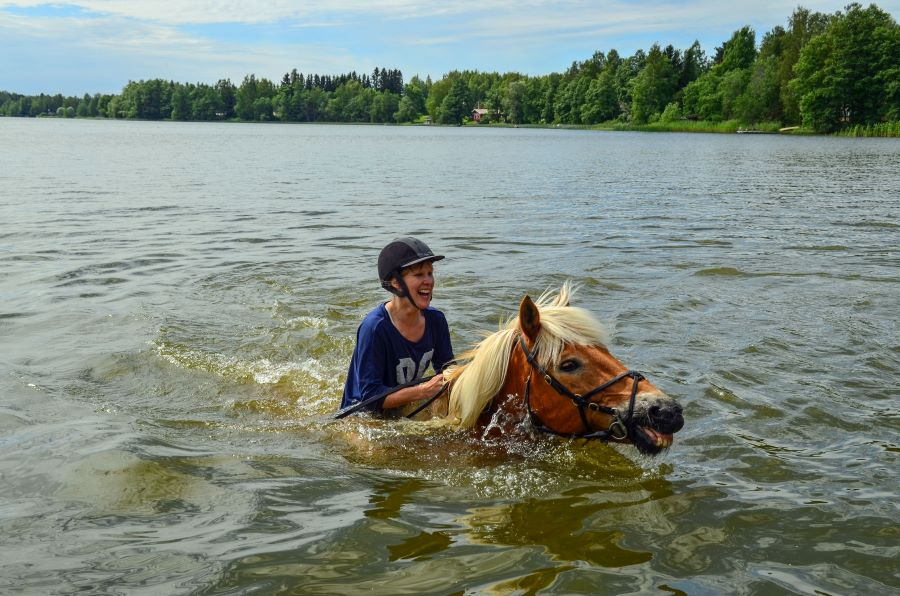 Woman riding a swimming horse in a lake